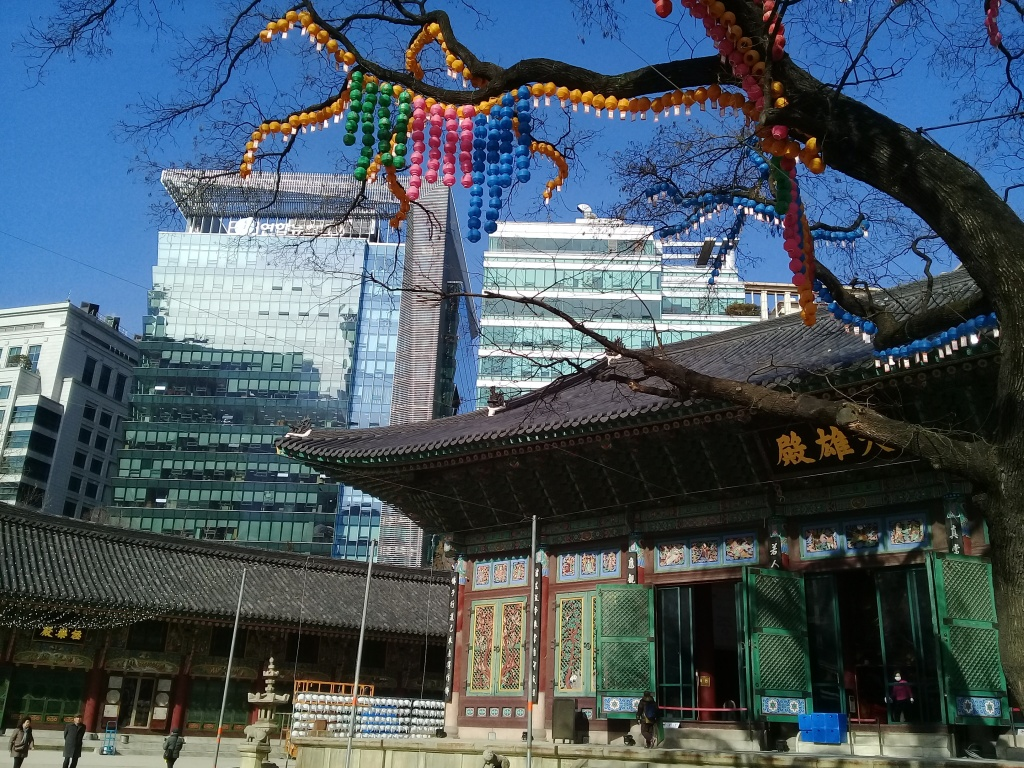 A korean Buddhist temple with a colorfully decorated tree above and two glass tall buildings in the background.