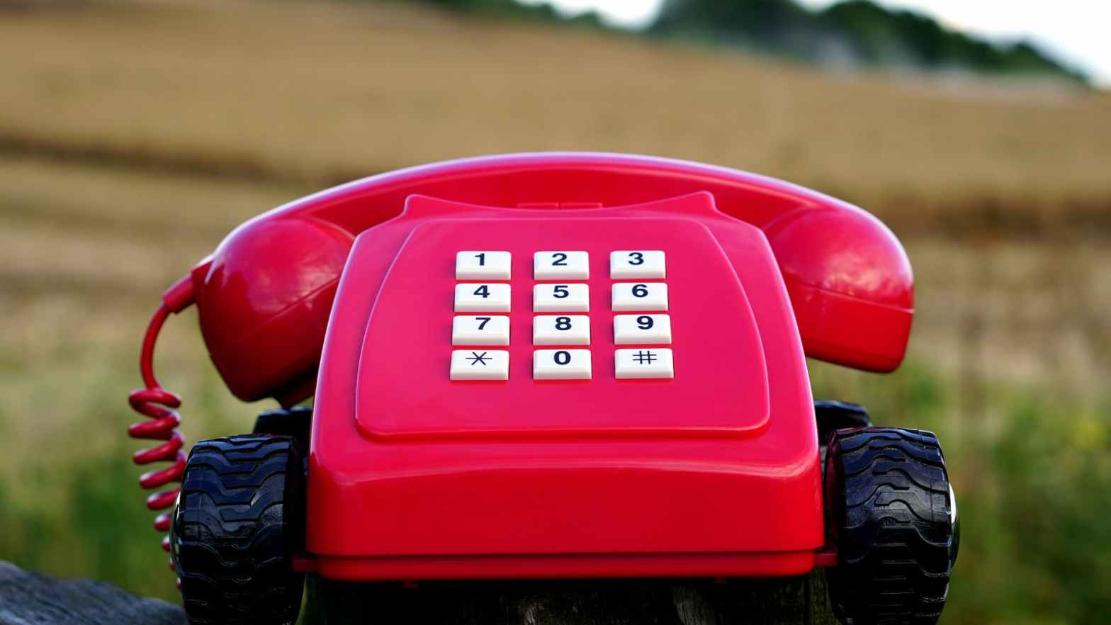 red rotary phone with black wheels