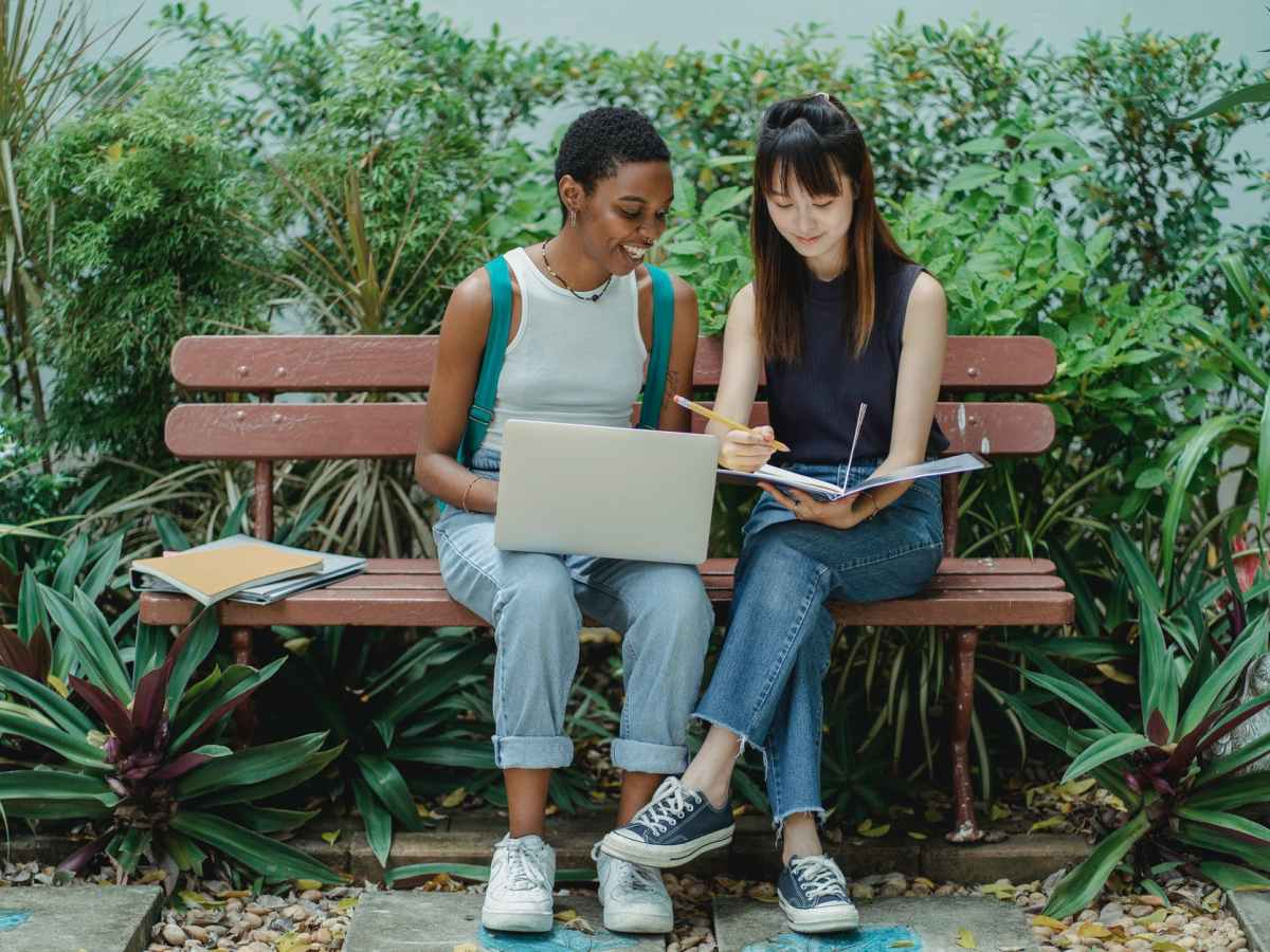 two girls studying in a green park